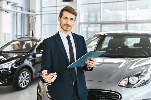 A man in a suit standing in front of a car